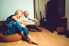 Ζεύγος διασκέδασης που απολαμβάνει τα παιχνίδια στον υπολογιστή στη TV Στοκ Εικόνα