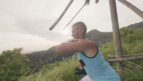 Ζεύγος ικανότητας που κάθεται οκλαδόν η υπαίθρια κατάρτιση στο πράσινο υπόβαθρο ορεινών περιοχών Στάση οκλαδόν κατάρτισης αθλητών φιλμ μικρού μήκους
