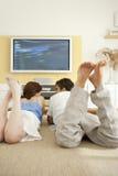 ζεύγος κάτω από το πάτωμα που βάζει την προσοχή TV Στοκ εικόνα με δικαίωμα ελεύθερης χρήσης