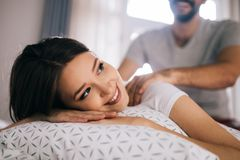 Ζεύγος και καλές στιγμές στο κρεβάτι Φίλος που δίνει το μασάζ για την όμορφη φίλη του στοκ φωτογραφία