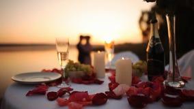 Ζεύγος κατά τη ρομαντική ημερομηνία στο εστιατόριο παραλιών στο ηλιοβασίλεμα απόθεμα βίντεο