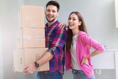Ζεύγος με τα ανοιγμένα κιβώτια στο νέο σπίτι στοκ εικόνα
