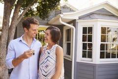 Ζεύγος με τα κλειδιά που στέκονται έξω από το νέο σπίτι στοκ εικόνα με δικαίωμα ελεύθερης χρήσης