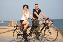 Ζεύγος με τα ποδήλατα σε μια παραλία πόλεων Στοκ Φωτογραφίες