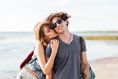 Ζεύγος με τα σακίδια πλάτης που στέκονται και που φιλούν στην παραλία στοκ εικόνες με δικαίωμα ελεύθερης χρήσης