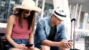 Ζεύγος με τα τηλέφωνα που περιμένει στον αερολιμένα απόθεμα βίντεο