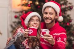 Ζεύγος με τα φλυτζάνια στο christmastime Στοκ εικόνα με δικαίωμα ελεύθερης χρήσης