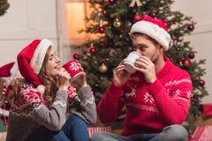 Ζεύγος με τα φλυτζάνια στο christmastime Στοκ Εικόνα