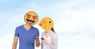 Ζεύγος με τα emojis πέρα από τα πρόσωπα που χρησιμοποιούν τα κινητά τηλέφωνα στοκ εικόνα