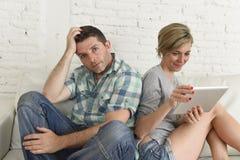 Ζεύγος με την ευτυχή σύζυγο που χρησιμοποιεί Διαδίκτυο app στο ψηφιακό μαξιλάρι ταμπλετών που αγνοεί τον τρυπημένο και λυπημένο σ Στοκ εικόνα με δικαίωμα ελεύθερης χρήσης