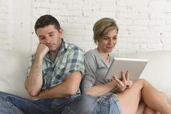 Ζεύγος με την ευτυχή σύζυγο που χρησιμοποιεί Διαδίκτυο app στο ψηφιακό μαξιλάρι ταμπλετών που αγνοεί τον τρυπημένο και λυπημένο σ Στοκ Φωτογραφίες