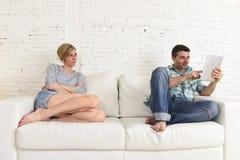 Ζεύγος με τον ευτυχή σύζυγο που χρησιμοποιεί Διαδίκτυο app στο ψηφιακό μαξιλάρι ταμπλετών που αγνοεί την τρυπημένη και λυπημένη σ Στοκ φωτογραφία με δικαίωμα ελεύθερης χρήσης