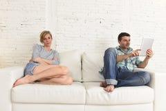 Ζεύγος με τον ευτυχή σύζυγο που χρησιμοποιεί Διαδίκτυο app στο ψηφιακό μαξιλάρι ταμπλετών που αγνοεί την τρυπημένη και λυπημένη σ Στοκ Εικόνες