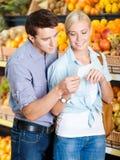 Ζεύγος με τον κατάλογο αγορών ενάντια στους σωρούς των φρούτων στοκ εικόνα