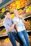 Ζεύγος με τον κατάλογο αγορών ενάντια στους σωρούς των φρούτων στοκ εικόνες