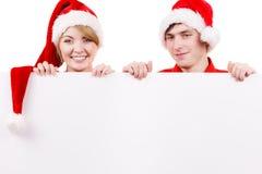 Ζεύγος με τον κενό κενό πίνακα εμβλημάτων Χριστούγεννα Στοκ εικόνες με δικαίωμα ελεύθερης χρήσης