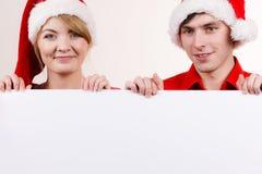 Ζεύγος με τον κενό κενό πίνακα εμβλημάτων Χριστούγεννα Στοκ Εικόνες