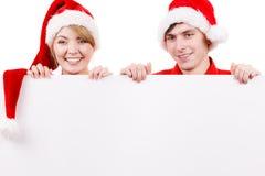 Ζεύγος με τον κενό κενό πίνακα εμβλημάτων Χριστούγεννα Στοκ Φωτογραφίες