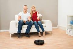 Ζεύγος με τον τηλεχειρισμό και ρομποτική ηλεκτρική σκούπα Στοκ εικόνα με δικαίωμα ελεύθερης χρήσης