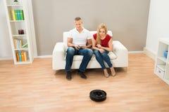 Ζεύγος με τον τηλεχειρισμό και ρομποτική ηλεκτρική σκούπα Στοκ φωτογραφία με δικαίωμα ελεύθερης χρήσης