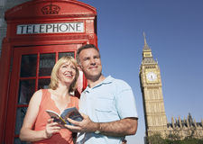 Ζεύγος με τον τουριστικό οδηγό ενάντια στον τηλεφωνικό θάλαμο του Λονδίνου και τη ρυμούλκηση Big Ben Στοκ Εικόνες