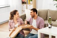 Ζεύγος με το κρασί που τρώει τη take-$l*away πίτσα στο σπίτι στοκ φωτογραφία με δικαίωμα ελεύθερης χρήσης