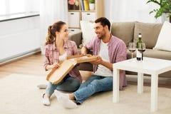 Ζεύγος με το κρασί που τρώει τη take-$l*away πίτσα στο σπίτι στοκ φωτογραφίες με δικαίωμα ελεύθερης χρήσης