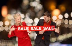 Ζεύγος με το κόκκινο σημάδι πώλησης πέρα από τα φω'τα Χριστουγέννων Στοκ φωτογραφία με δικαίωμα ελεύθερης χρήσης