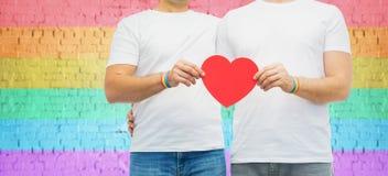Ζεύγος με το ομοφυλοφιλικό ουράνιο τόξο υπερηφάνειας wristbands και την καρδιά στοκ φωτογραφίες