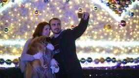 Ζεύγος με το σκυλί cutie που κάνει selfie υπαίθρια το μέτωπο του τεράστιου χριστουγεννιάτικου δέντρου Καλή οικογένεια διάθεσης απόθεμα βίντεο