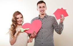 Ζεύγος με το σπίτι εγγράφου και το σύμβολο αγάπης καρδιών Στοκ Εικόνες