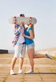 Ζεύγος με skateboard που φιλά υπαίθρια Στοκ φωτογραφία με δικαίωμα ελεύθερης χρήσης