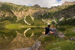Ζεύγος μπροστά από τη λίμνη/ερωτευμένη στάση ζεύγους μπροστά από τα βουνά και τη λίμνη από τη Βαυαρία, Γερμανία Στοκ Φωτογραφίες