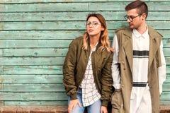 Ζεύγος μόδας στα γυαλιά με τα γυαλιά στα πράσινα ενδύματα που θέτουν το ο Στοκ εικόνες με δικαίωμα ελεύθερης χρήσης