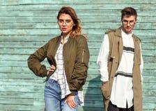Ζεύγος μόδας στα γυαλιά με τα γυαλιά στα πράσινα ενδύματα που θέτουν το ο Στοκ εικόνα με δικαίωμα ελεύθερης χρήσης