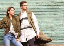 Ζεύγος μόδας στα γυαλιά με τα γυαλιά στα πράσινα ενδύματα που θέτουν το ο Στοκ Εικόνα