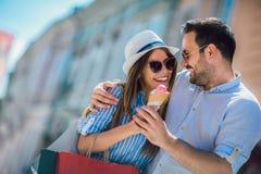 Ζεύγος που έχει την ημερομηνία και που τρώει το παγωτό μετά από να ψωνίσει στοκ εικόνες