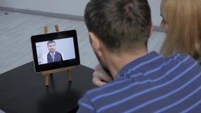 Ζεύγος που έχει την τηλεοπτική συνομιλία με τον οικογενειακό γιατρό σε απευθείας σύνδεση διαβουλεύσεις απόθεμα βίντεο