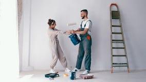 Ζεύγος που έχει τη διασκέδαση εργαζόμενος και χρωματίζοντας το νέο διαμέρισμά τους απόθεμα βίντεο