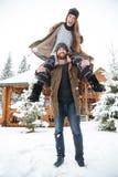 Ζεύγος που έχει τη διασκέδαση κοντά στην καμπίνα κούτσουρων το χειμώνα Στοκ εικόνες με δικαίωμα ελεύθερης χρήσης