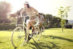 Ζεύγος που έχει τη διασκέδαση με το ποδήλατο στις διακοπές στη λίμνη