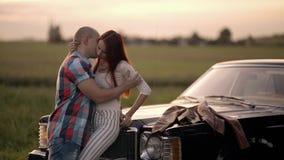 Ζεύγος που αγκαλιάζει και που φιλά στη φύση κοντά σε ένα αναδρομικό αυτοκίνητο φιλμ μικρού μήκους