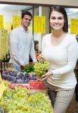 Ζεύγος που αγοράζει τα φρέσκα εποχιακά φρούτα στην αγορά Στοκ Εικόνα