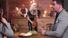 Ζεύγος που ακούει μια ζωντανή απόδοση saxophone απόθεμα βίντεο