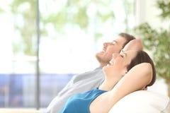 Ζεύγος που αναπνέει και που στηρίζεται στο σπίτι στοκ εικόνες