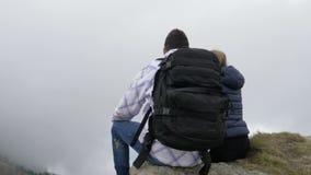 Ζεύγος που απολαμβάνει τη συνεδρίαση εξόρμησης βουνών στον υψηλό απότομο βράχο και που θαυμάζει την ομορφιά της φύσης με τα misty φιλμ μικρού μήκους