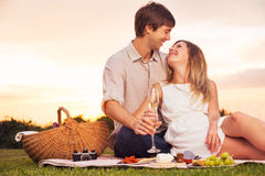 Ζεύγος που απολαμβάνει το ρομαντικό πικ-νίκ ηλιοβασιλέματος Στοκ φωτογραφία με δικαίωμα ελεύθερης χρήσης