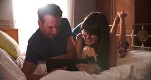 Ζεύγος που βρίσκεται στο κρεβάτι που χρησιμοποιεί την ψηφιακή ταμπλέτα απόθεμα βίντεο