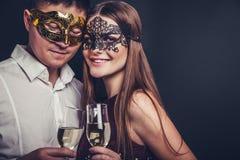 Ζεύγος που γιορτάζει τη νέα σαμπάνια κατανάλωσης παραμονής έτους ` s στο κόμμα μεταμφιέσεων στοκ εικόνα με δικαίωμα ελεύθερης χρήσης