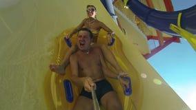 Ζεύγος που γλιστρά κάτω από μια φωτογραφική διαφάνεια νερού στη δημόσια πισίνα απόθεμα βίντεο